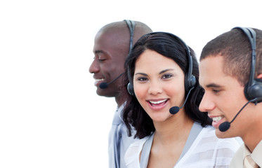 Portrait of a brunette woman and her team working in a call cent