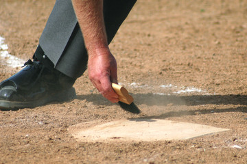 Baseball Umpire Brushing off Home Plate