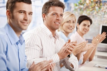 Business people clapping at meeting