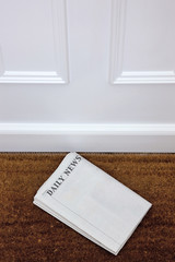 Blank newspaper lying on a doormat.