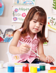 Child with picture and brush in play room. Preschooler.