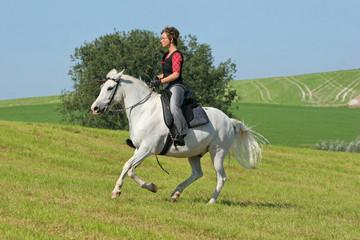 Frau reitet Pferd