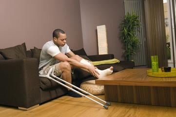 Homme platré assis dans son salon