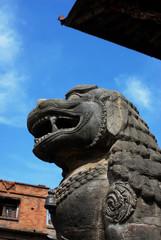 Ancient lion sculpture under blue sky
