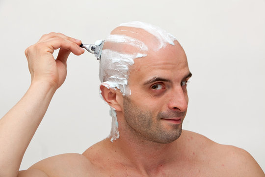 Young man shaving his head with razorblade