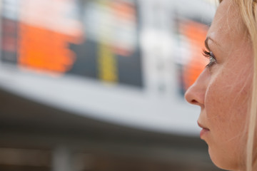 Woman watching departure board at airport