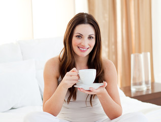 Charming woman drinking coffee sitting on bed