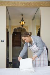 Femme de chambre dans un hôtel - plier des serviettes