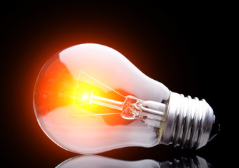 Photo of light bulb on black.
