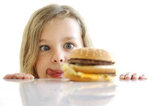 Fillette devant un hamburger.
