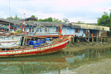 Fishermen's huts and old fishing boat in South of Thailand