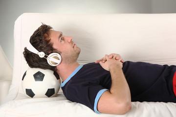 junger mann mit kopfhörern hört musik uns liegt auf fussball