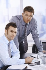 Portrait of businessmen at desk