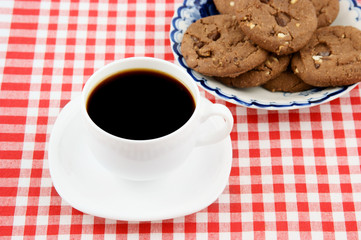 White cup of coffee and cookies on tablecloth