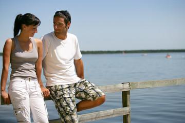 Couple profitant du soleil assis sur un ponton