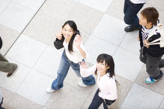 手を振る女子大学生