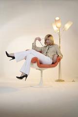 Frau im Sessel vor Stehlampe