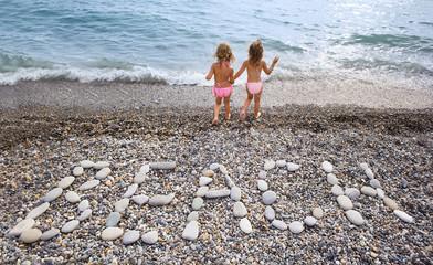 Inscription from stones BEACH at stony coast, two girl