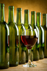 Glass of red wine with bottles