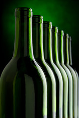 Row of bottles with green background