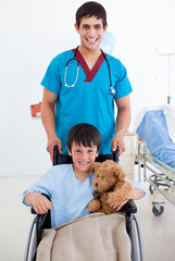 Portrait of a cute little boy sitting on wheelchair and a doctor