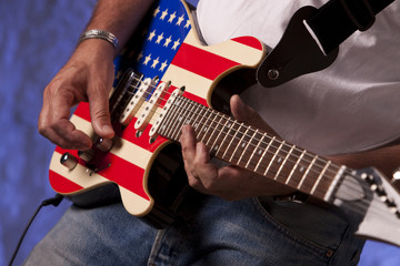 man playing guitar in front of a backround