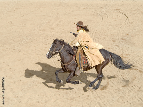 Wall mural Cowboy riding a horse at full gallop with gun in hand