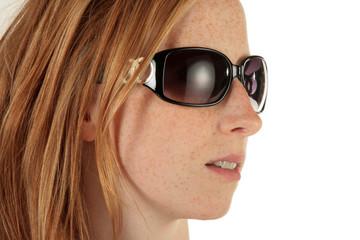Rothaarige Frau mit Sonnebrille blickt zur Seite