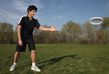 Young man playing frisbee in the park