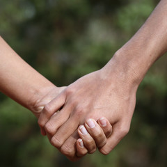 Young couple holding hands (closeup) while outdoors in a park.