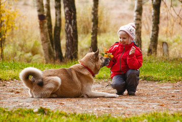 Little girl playing with her dog in autumn forest
