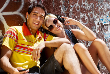 Young happy couple sitting on sidewalk