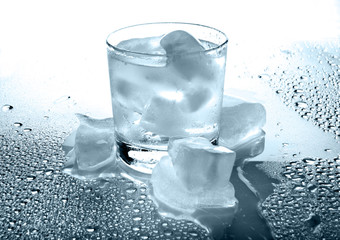 Glass with a drink and ice on a white background