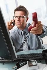 Businessman talking on cell holding landline