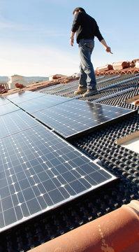 Ouvrier sur un toit installant des panneaux solaires