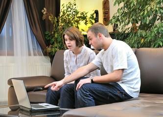 Frère et soeur surpris devant un ordinateur