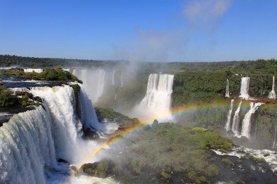 Iguazu waterfalls with rainbow on a sunny day.