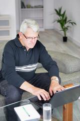 Homme senior devant ordinateur portable