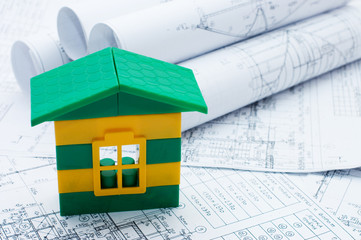 Close-up of toy house model on blueprints
