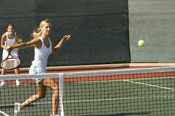 doubles tennis player hitting tennis ball with backhand