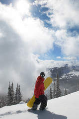 teenage boy (16-19) holding snowboard hiking up snow covered slope full length