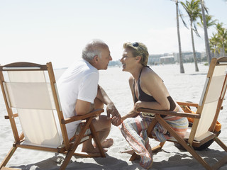 senior couple on sunloungers on tropical beach side view