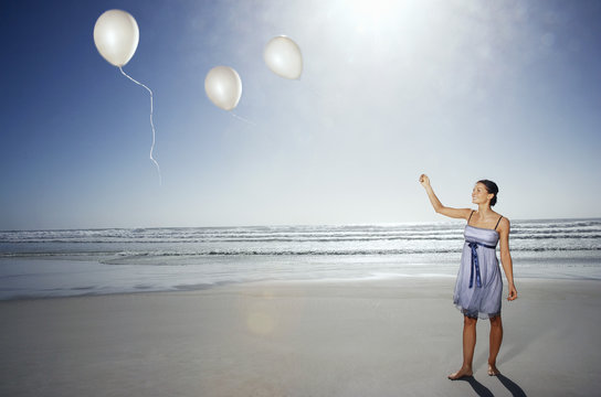 woman letting balloons go on beach elevated view