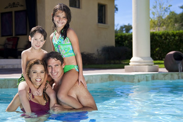 Happy Family With Two Children Playing In A Swimming Pool