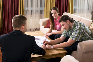 Happy couple meeting with agent at home