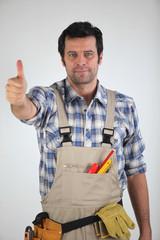 Ouvrier avec une sacoche à outils levant le pouce