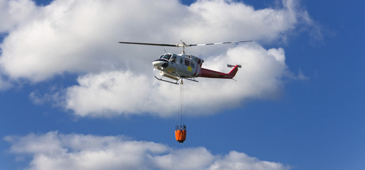 Fire fighting helicopter with waterbag on his way to combat the