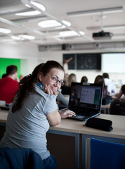young pretty female college student sitting in a classroom full