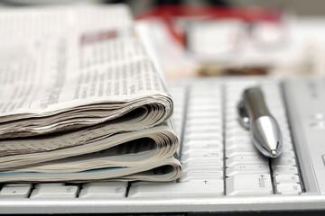Financial Newspapers on laptop keyboard