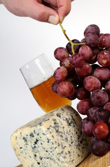 human hand arranging red grapes and cheese